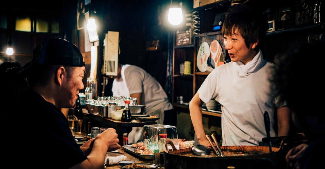 A restaurant owner interacts with a happy customer.