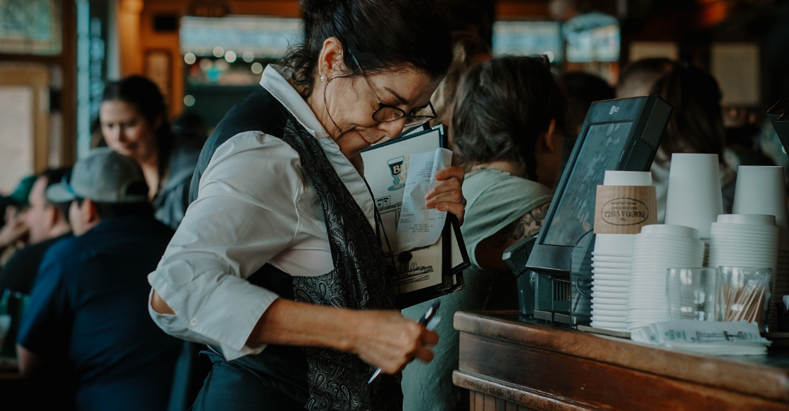 A restaurant worker uses a credit card processor.