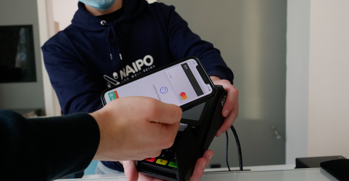 A freelancer accepts a payment from a customer on a payment terminal.